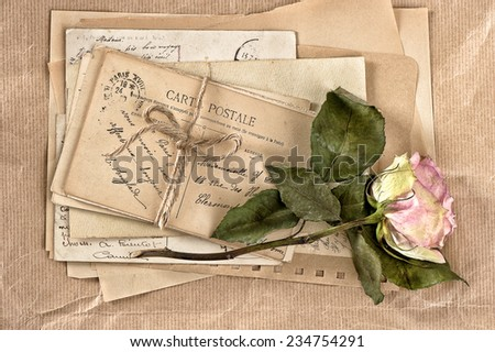 dried rose flower and old letters. vintage postcards and envelopes. scrapbook - stock photo
