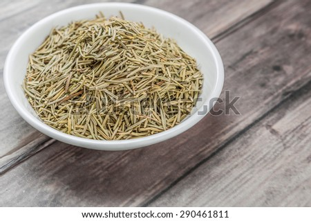 Dried rosemary herb in white bowl on weathered wooden background