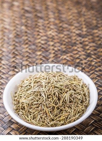 Dried rosemary herb in white bowl on wicker background
