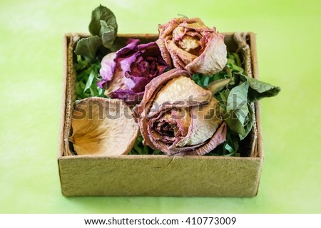Dried roses in brown box with green background - stock photo