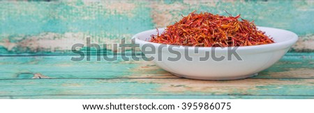 Dried safflower in white bowl over wooden background - stock photo