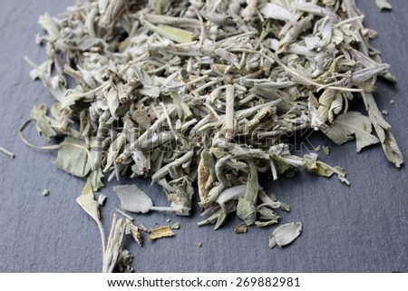 Dried sage plant (salvia officinalis) leaves (whole herb) for incense or herbal tea infusion on a grey slate stone background, natural feeling used by the ancient native indians for rituals  - stock photo