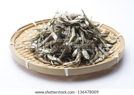 Dried sardine on bamboo basket - stock photo