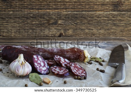 Dried sausages and spices on paper, on wooden background. - stock photo