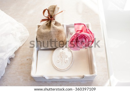 Dried scented herbs in red decorative bag and rose in porcelain plate - stock photo