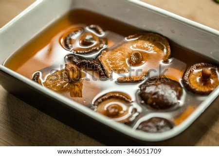 Dried shiitake mushroom in transparent bowl with water - stock photo