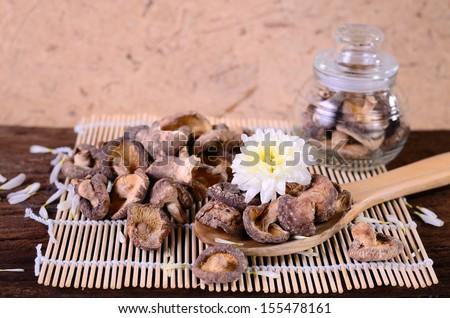 Dried shiitake mushroom (Lentinula edodes) on old wood background - stock photo