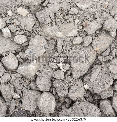 Dried soil covered with stones and dust as a background texture - stock photo