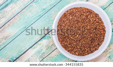 Dried South African rooibos herbal tea in white bowl over wooden background