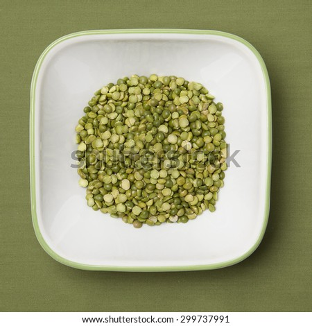 Dried split peas in white bowl, green background - stock photo