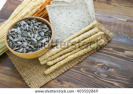 dried sunflower seeds ,bread with spikelets on wooden background - stock photo