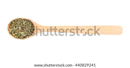 Dried tarragon in spoon on white background - stock photo