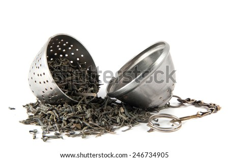 Dried tea in tea-strainer on white background - stock photo