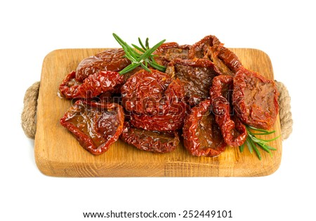 dried tomatoes on wooden cutting board - stock photo
