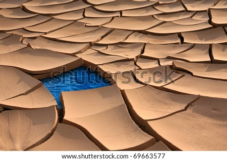 Dried up river bed revealing water underneath - stock photo