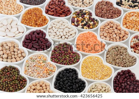 Dried vegetable pulses health food selection in heart shaped porcelain china dishes over white background. - stock photo