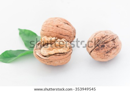 Dried walnuts with leaves on white background - stock photo