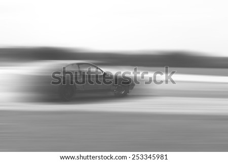 drift car motion blur on vintage black and white - stock photo