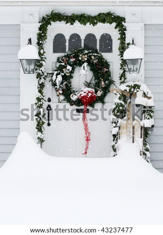 drifted snow in front of home entrance decorated for holidays - stock photo