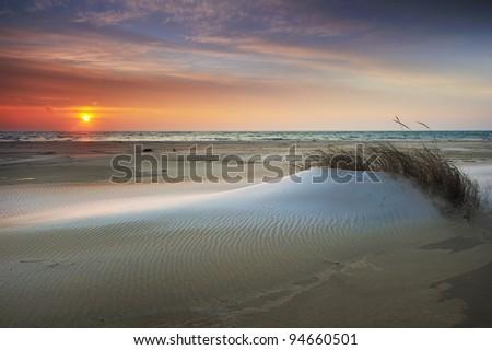 Drifting snow on a Lake Huron beach winter sunrise.  Tawas Point State Park, Michigan USA - stock photo