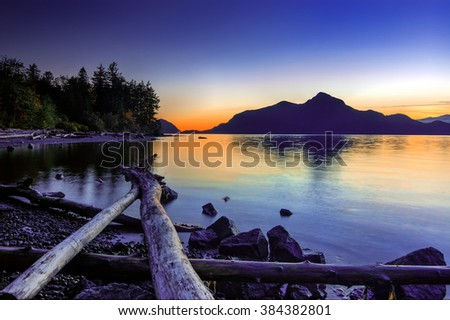 Driftwood and pebbles on the shore, sun behind the mountains creating a blue hue - stock photo