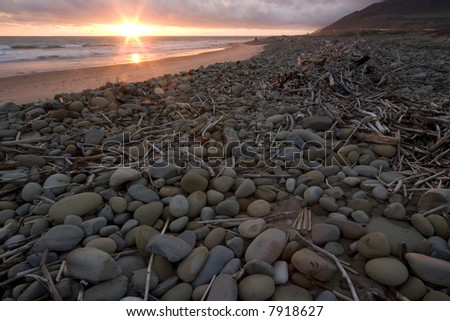 Driftwood and stones left on beach after a storm at sunset in Ventura, Ca. - stock photo