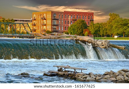 driftwood log on top of dam on the Grand river in grand rapids, michigan - stock photo