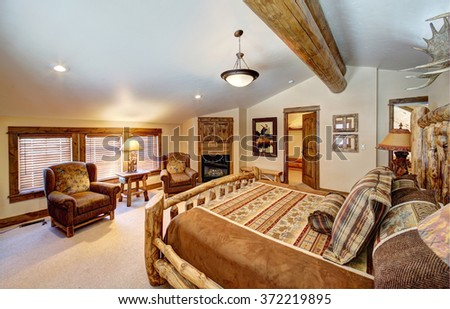 Driggs, Idaho, USA Nov. 12, 2014 A luxurious bedroom, with a fireplace and king sized bed, in a modern log cabin in the mountains. - stock photo