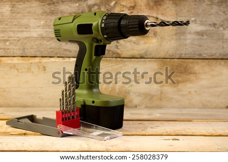 Drill and set of drill bits over wooden background - stock photo