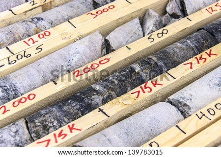 Drill core where the black rock is mineralized uranium - stock photo