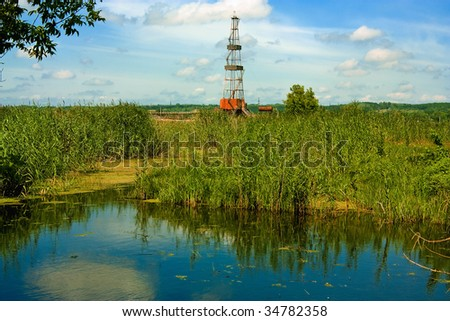Drill derrick in the natural landscape - stock photo