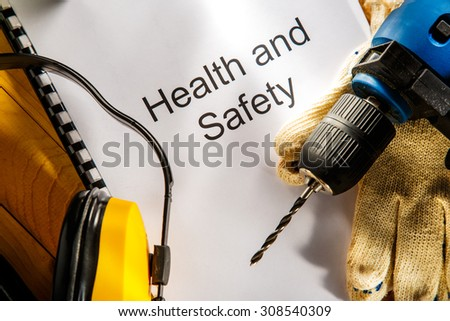 Drill, earphones and gloves on wooden background - stock photo