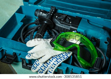 Drill, gloves and goggles in the box - stock photo