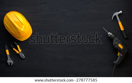 drill, helmet, hammer, pliers and construction tools on black wooden background - stock photo