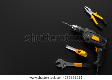 drill, wrench and other construction tools on the black background textures - stock photo