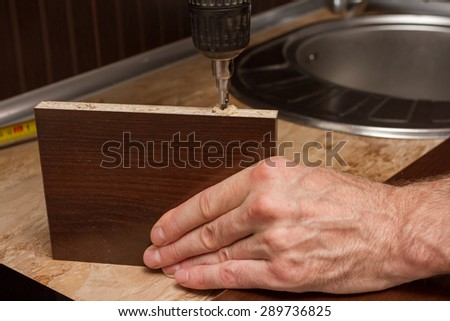 Drilling chipboard. - stock photo