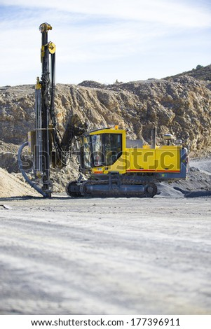Drilling holes for demolition in a rock quarry - stock photo