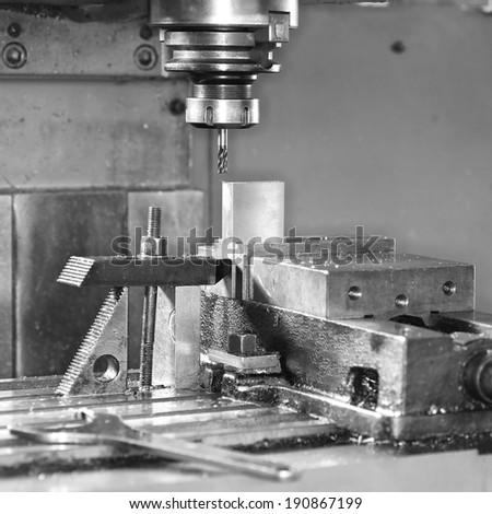 Drilling Machine automatically processing a metallic part.  - stock photo