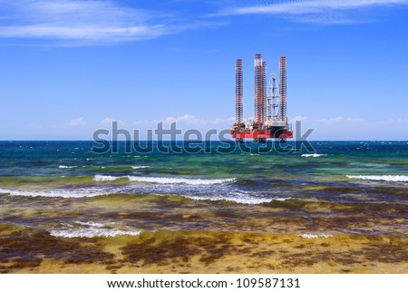 Drilling platform in the sea against a blue sky - stock photo