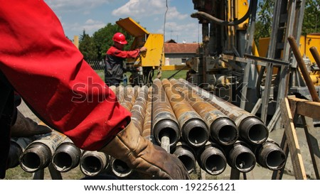 Drilling rig and two oil workers. Oil and gas industry. Oil drilling rig workers lifting drill pipe. - stock photo