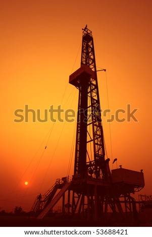Drilling rig at sunset - stock photo
