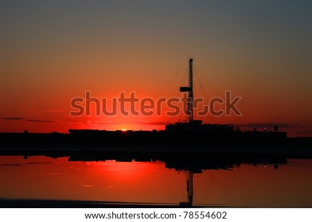 Drilling rig is on sunset in Kazakhstan oil field. - stock photo