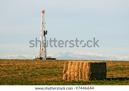 Drilling rig set up in an alfalfa field east of the Rocky Mountains in central Colorado, USA. - stock photo