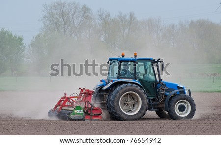 DRIMMELEN, NORTH-BRABANT, NETHERLANDS - APRIL 27: Milling of a very dry field in Drimmelen, Netherlands on April 27, 2011. The soil is very dry in Holland because almost no rain has fallen lately. - stock photo