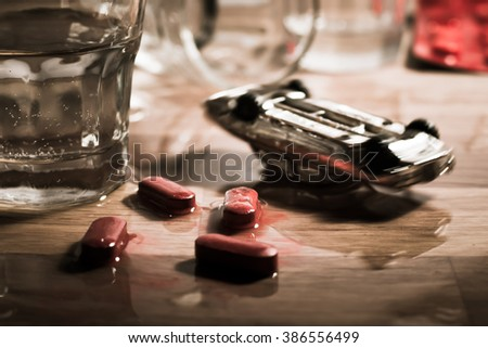 Drink and drive metaphor - toy car crash on a table with spilled shot of vodka and melting pills pretending accident victims.  - stock photo