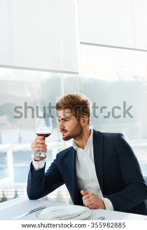 Drink. Closeup Of Elegant Handsome Young Man Drinking Red Wine Sitting In Luxury Gourmet Restaurant. Businessman Relaxing And Looking Through The Window. Success Celebration Dinner Concept - stock photo
