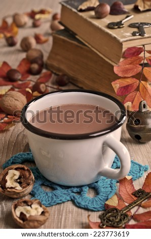 Drink light brown color in the circle on the background of fallen leaves and old books