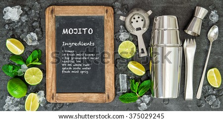 Drink making tools and ingredients for cocktail. Lime and mint leaves. Chalkboard with recipe text Mojito - stock photo