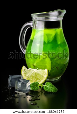 drink of kiwi and lime ice and mint in a glass jug isolated on black - stock photo