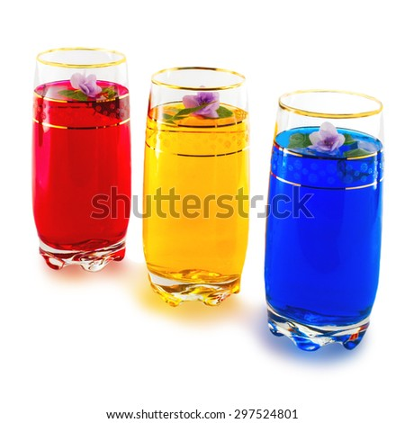 drink three colors and flowers, red, yellow, blue, white background - stock photo